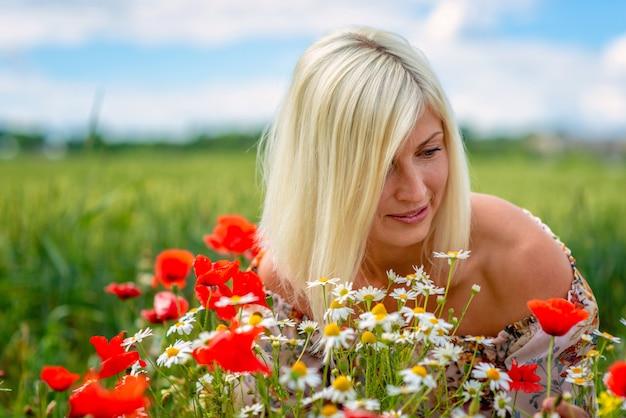 Een mooie, aantrekkelijke, blonde vrouw verzamelt weidebloemen aan de rand van het veld. zachte focus.