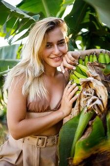 Een mooie aantrekkelijke jonge vrouw staat in de buurt van een bananenboom, een meisje gekleed in een zwempak loopt op een bananenplantage, exotische planten