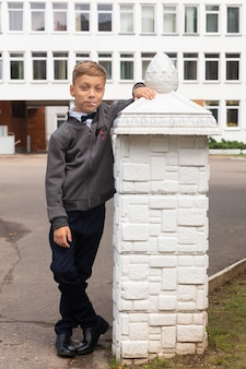 Een mooie achtjarige jongen in een schooluniform, een zwarte broek en een wit overhemd met vlinderdas poseert op het schoolplein.