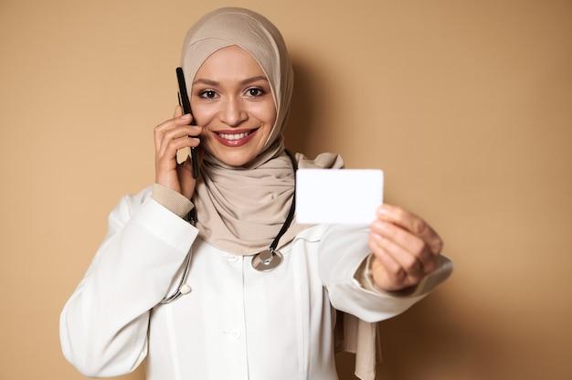 Een mooie arabische moslimvrouw, arts die door de mobiele telefoon spreekt en een witte lege plastic kaart van de verzekering toont aan de camera.