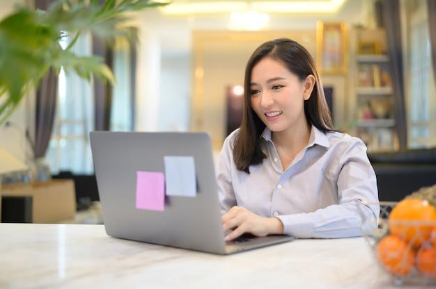 Een mooie aziatische bedrijfsvrouw werkt thuis met haar computer