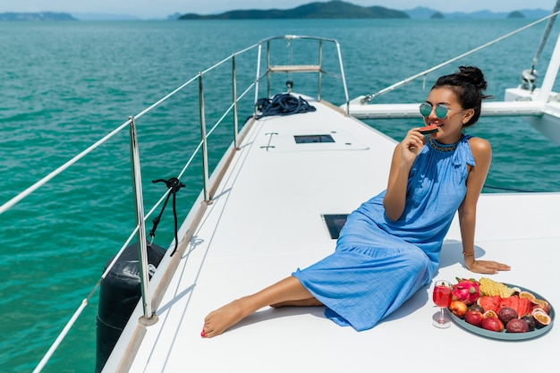 Een mooie aziatische dame in een blauwe jurk op een jacht drinkt champagne en eet fruit