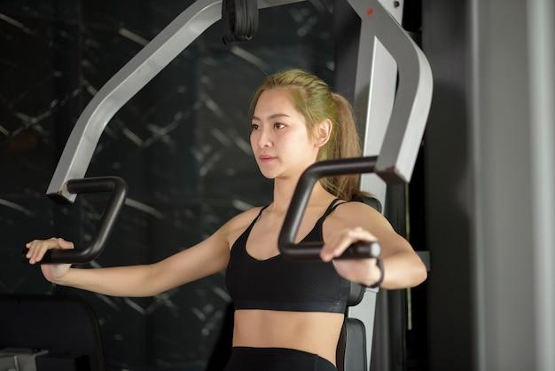 Een mooie aziatische fitness vrouw traint met sportartikelen in de fitnessruimte. fitness- en gezondheidsconcept.