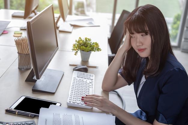 Een mooie aziatische vrouw die een donkerblauw pak draagt, zit aan een bureau in een modern kantoor en werkt stress