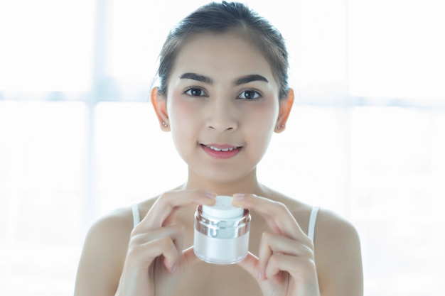 Een mooie aziatische vrouw die een huidverzorgingsproduct, vochtinbrengende crème of lotion gebruikt en haar droge teint verzorgt. hydraterende crème in vrouwelijke handen.