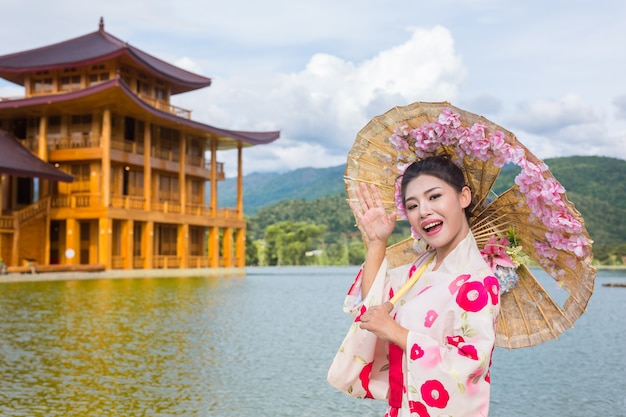 Een mooie aziatische vrouw die een japanse kimono, traditioneel kledingsconcept draagt.
