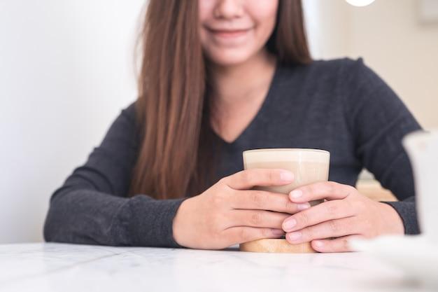 Een mooie aziatische vrouw die en het drinken van koffie met gevoel ontspannen in café