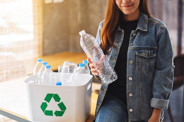 Een mooie aziatische vrouw die en recycleerbare huisvuil plastic flessen houdt thuis verzamelt in een afvalbak