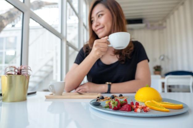 Een mooie aziatische vrouw die koffie drinkt en oranje cake met gemengd fruit eet in koffie