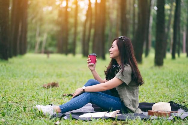 Een mooie aziatische vrouw die koffie drinkt terwijl ze in het park zit