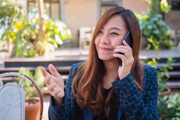 Een mooie aziatische vrouw die op een mobiele telefoon praat met een lachend gezicht in de buitenlucht