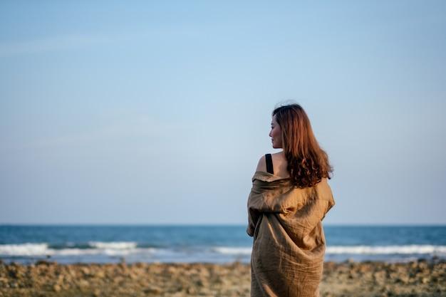 Een mooie aziatische vrouw die op het strand langs de kust loopt