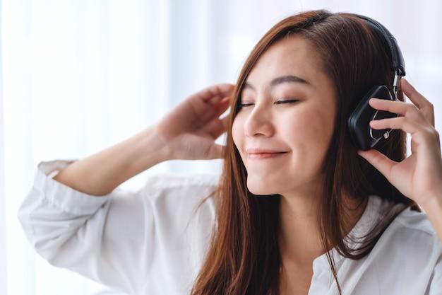 Een mooie aziatische vrouw geniet van het luisteren naar muziek met een hoofdtelefoon in de slaapkamer, geluk en ontspanning concepten