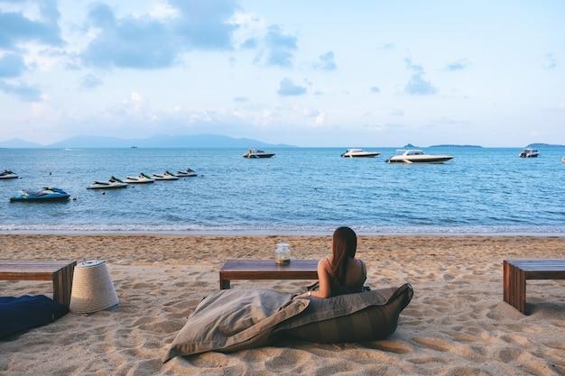 Een mooie aziatische vrouw geniet van het zitten en ontspannen op het strand aan de kust