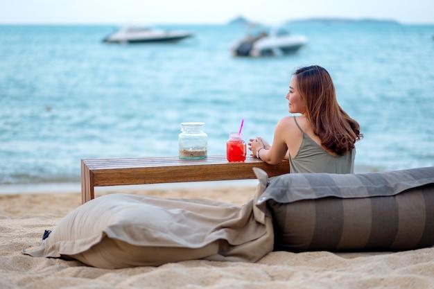 Een mooie aziatische vrouw geniet van zittend op het strand aan de kust