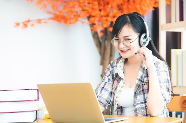 Een mooie aziatische vrouw in thailand met een bril en een geruit overhemd, ze kijkt naar een laptopcomputer en heeft een koptelefoon op tafel. in het concept van leren of teleconferenties via online.