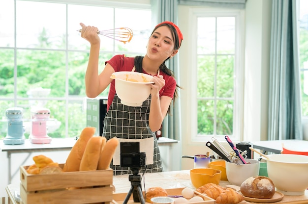 Een mooie aziatische vrouw maakt in haar huis bakkerij, livestreaming of neemt video op sociale media op