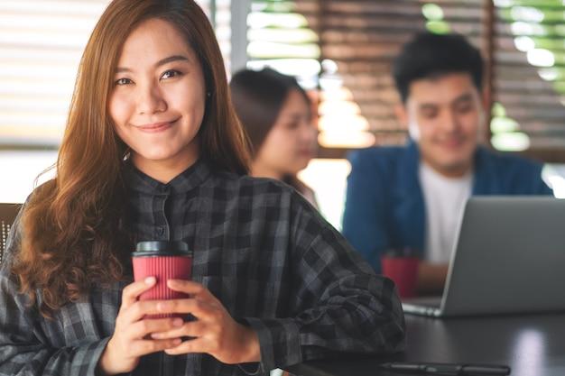 Een mooie aziatische vrouw met een papieren koffiekopje met collega's die op de achtergrond aan een laptop werken