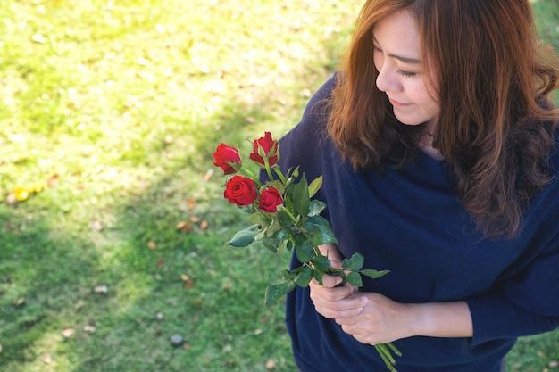 Een mooie aziatische vrouw met rode rozen bloeien in groene tuin met een gelukkig gevoel op valentijnsdag