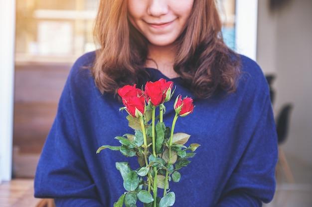 Een mooie aziatische vrouw met rode rozen bloeien met een gelukkig gevoel op valentijnsdag