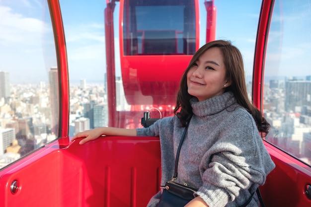 Een mooie aziatische vrouw rijdt op een rood reuzenrad in japan