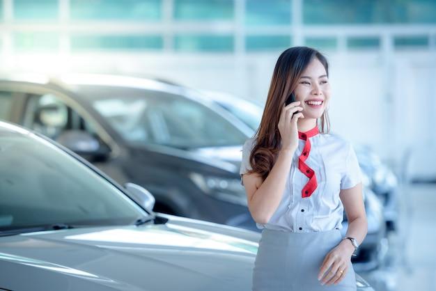 Een mooie aziatische vrouw verkoopt graag een nieuwe auto in de showroom en praat graag via de telefoon. enthousiast over het goede nieuws online in de showroom.