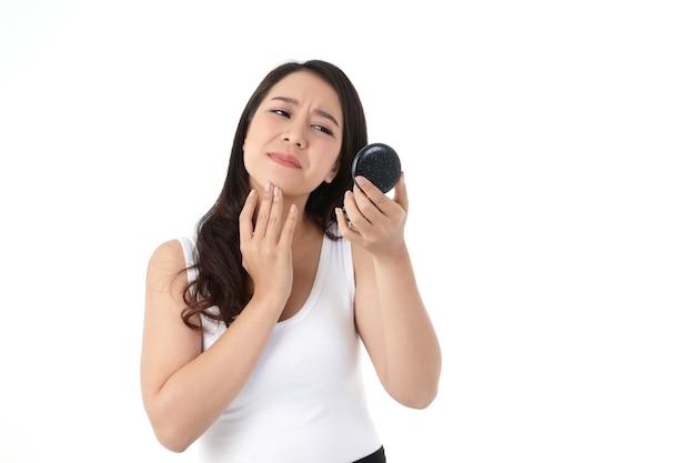 Een mooie aziatische vrouw voelt zich gestrest. ze houdt een spiegel vast en kijkt naar acne op haar wangen. schoonheid concept, witte achtergrond