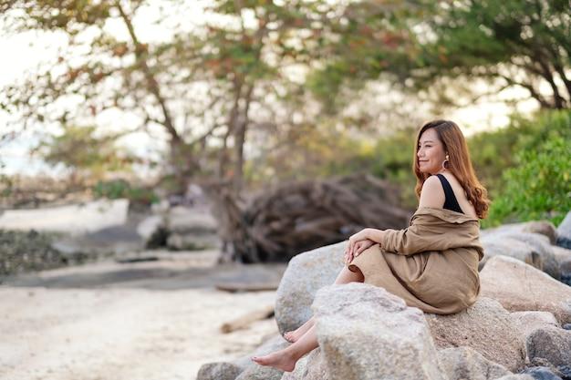 Een mooie aziatische vrouw zit graag op de rots aan de kust