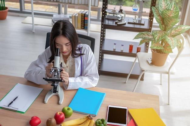 Een mooie aziatische vrouwelijke arts bekijkt een microscoop op een modern bureau met een groot glasvenster.