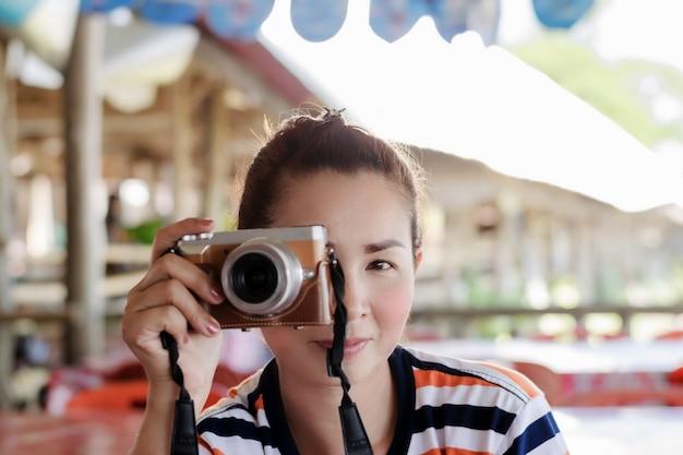 Een mooie aziatische vrouwelijke fotograaf heft een digitale camera op die aan het rechteroog is bevestigd om beelden op te nemen.