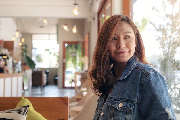 Een mooie aziatische vrouwenzitting in koffie met gelukkig gevoel
