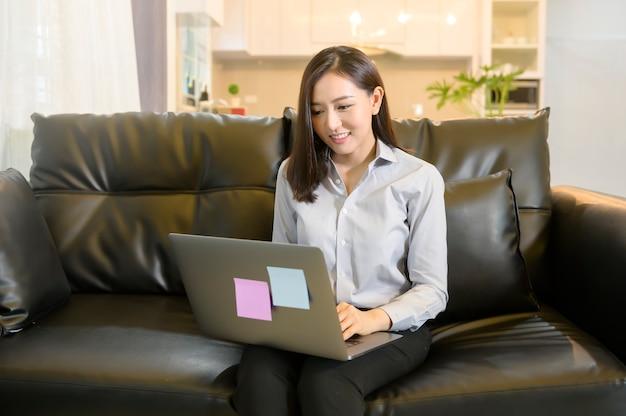 Een mooie aziatische zakenvrouw werkt thuis met haar computer, telecommunicatie, sociale afstand, werk vanuit huis concept.