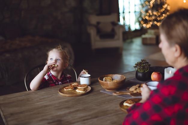 Een mooie baby heeft ontbijt met pannenkoeken van kwark en cacao