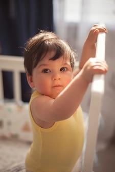 Een mooie baby in een geel lijfje is het waard om zich vast te houden aan een wieg bij het raam