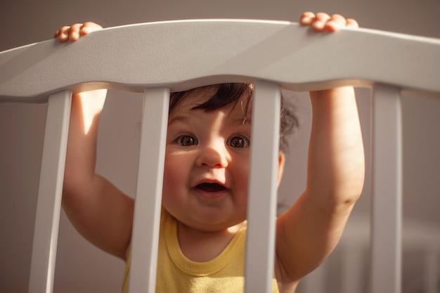 Een mooie baby in een geel lijfje is het waard om zich vast te houden aan een wieg en verstopt zich achter de tralies van het bed in de zon