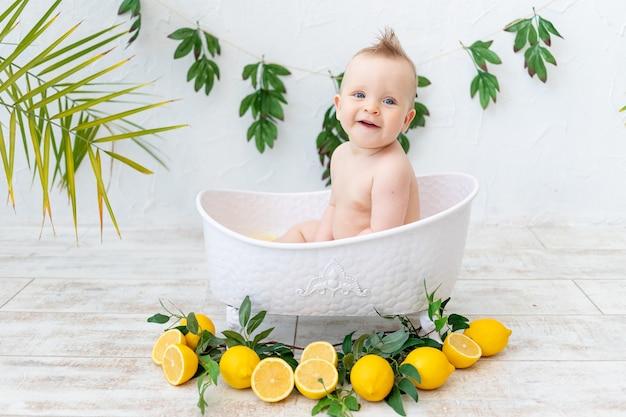 Een mooie babyjongen baadt in een bad met fruitcitroenen en glimlacht, het concept van hygiëne en wassen