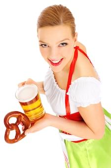 Een mooie beierse serveerster met een biertje en een krakeling op een witte achtergrond