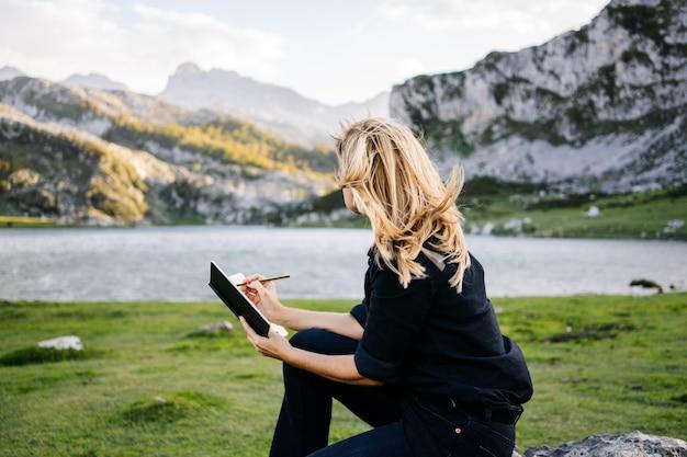 Een mooie blanke blonde vrouw schrijft en tekent op een notitieblok in een berglandschap met meer