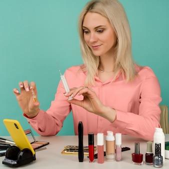 Een mooie blogger toont een injectiespuit en een ampul met een middel tegen veroudering in haar hand