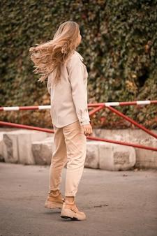 Een mooie blonde jonge vrouw loopt door de straat, ze draagt een spijkerbroek en een beige shirt. mooi meisje gekleed in casual stijl met een glimlach op haar gezicht voor een wandeling