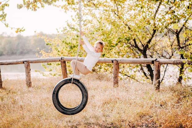 Een mooie blonde jongen in lichte kleren rijdt op een band op een boom en lachen.