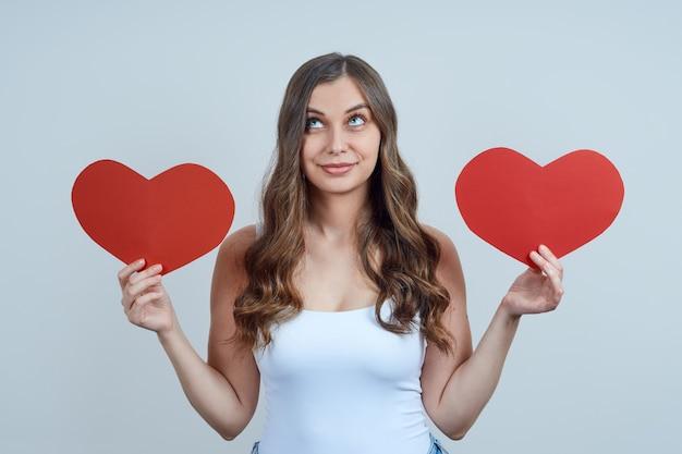 Een mooie blonde met krullen, houdt twee harten van papier vast, wordt opgezocht. fijne valentijnsdag. wereldhartdag.
