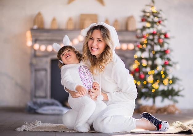 Een mooie blonde moeder en een kind in witte pluizige konijntjeskostuums lachen tegen de achtergrond van een kerstboom en een open haard. hoge kwaliteit foto