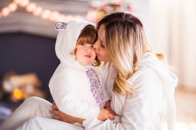 Een mooie blonde moeder kuste een kind in witte pluizige konijntjeskostuums tegen de achtergrond van een kerstboom en een open haard. hoge kwaliteit foto