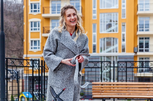 Een mooie blonde vrouw in een grijze jas met een borduurpatroon. de vrouw poseert op het balkon met een decoratief hek op een stedelijke achtergrond.