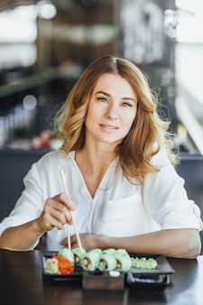 Een mooie blonde vrouw van middelbare leeftijd dineert met de rol van californië in een japans restaurant op het zomerterras