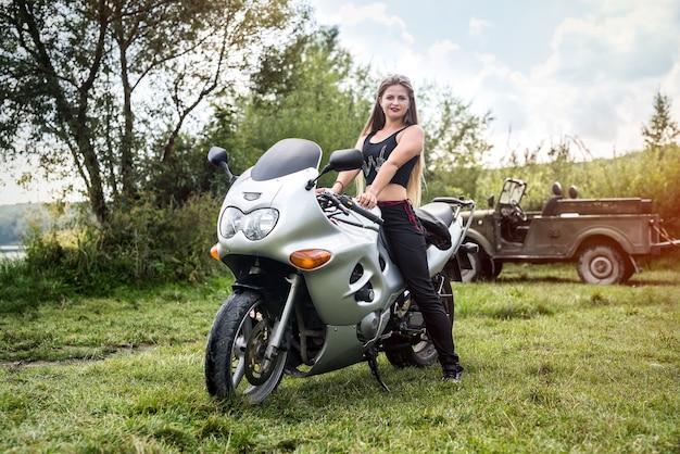 Een mooie blonde vrouw, zittend op een motorfiets