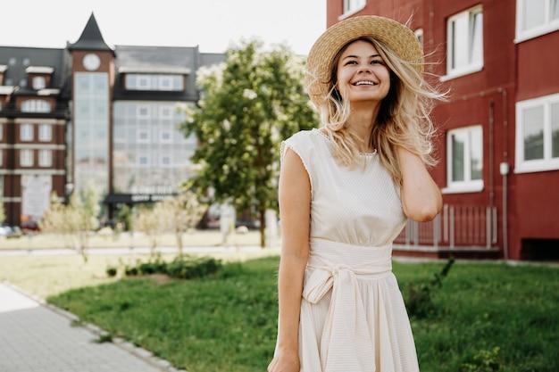 Een mooie blondine loopt door een europese stad. vrouw in witte jurk en strohoed, ze lacht en is blij