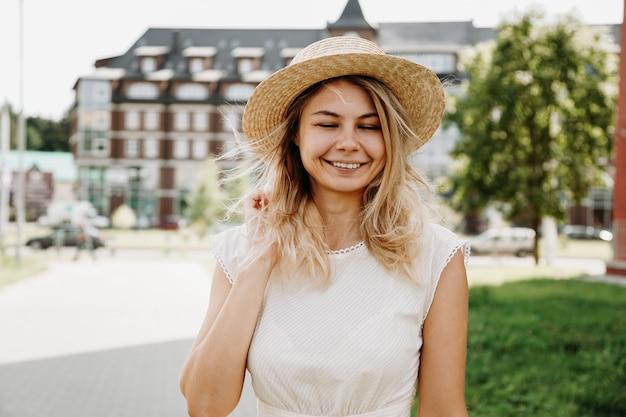 Een mooie blondine loopt door een europese stad. vrouw met gesloten ogen in witte jurk en strohoed, ze glimlacht en gelukkig