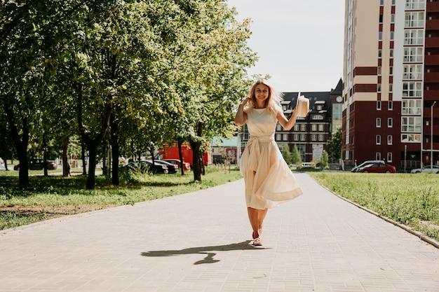 Een mooie blondine loopt door een stad. vrouw in witte jurk en strohoed